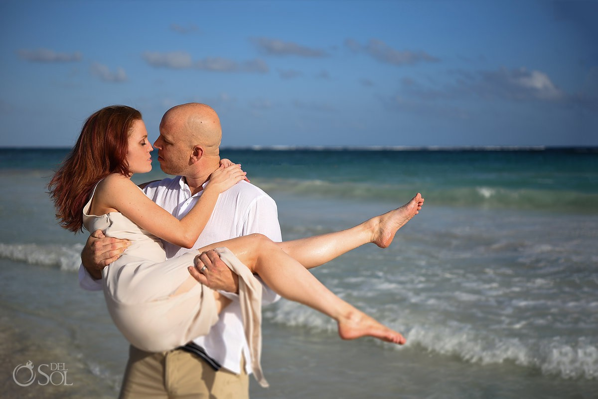 Husband carrying wife in his arms Romantic honeymoon portraits Dreams Tulum beach Riviera Maya Mexico