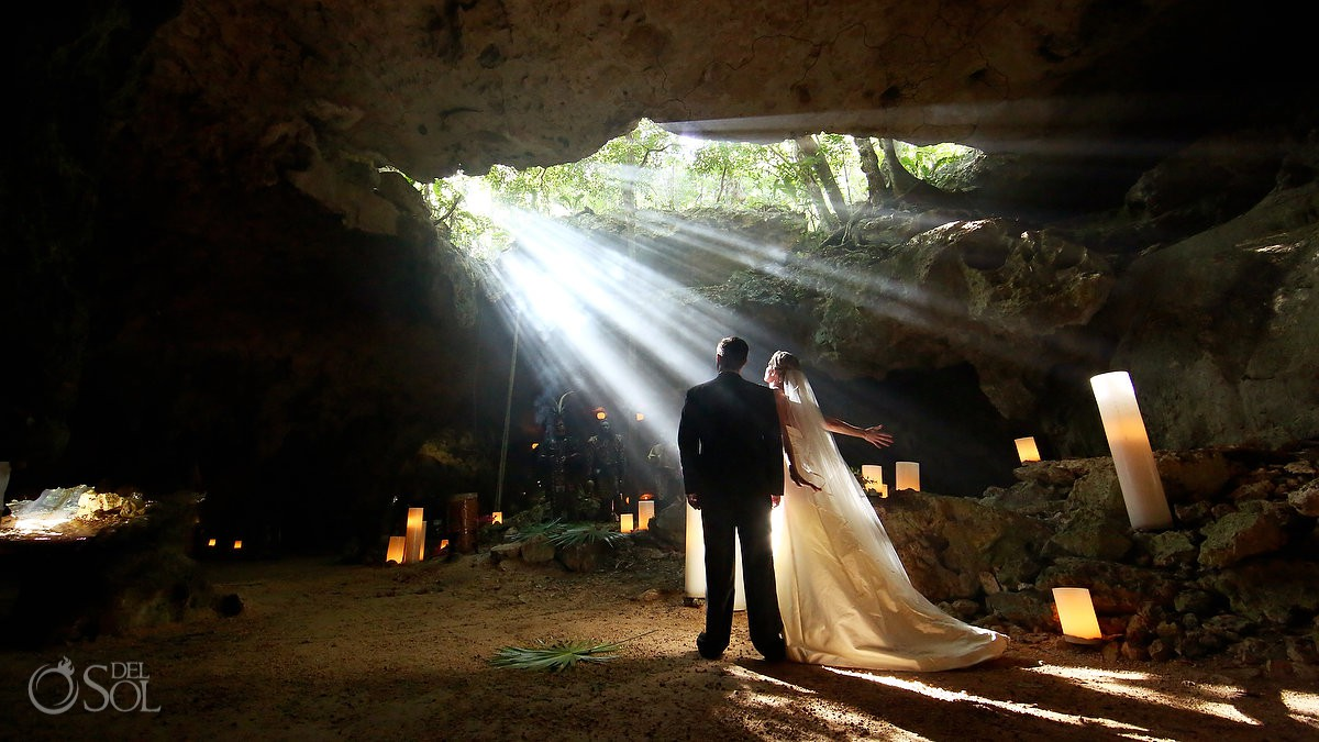 bride and groom connecting with nature inside cave vow renewal cenote Aktun Chen, Mexico