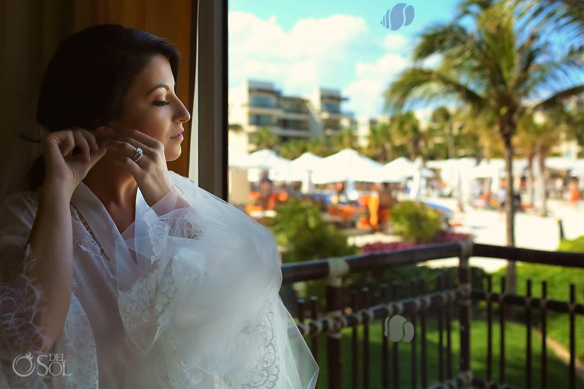 Destination Wedding bride getting ready putting earnings on Dreams Riviera Cancun Resort Mexico