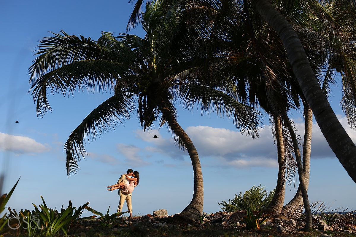 couple under palm trees with birds flying past Grand Sirenis Riviera Maya Save the Date Engagement Session