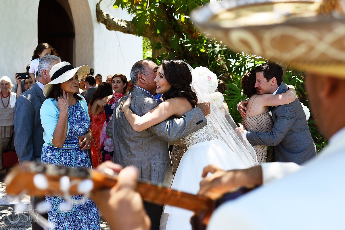 bride and groom hugging guests with mariachi playing outside St Francis Assisi Chapel Xcaret Playa del Carmen Mexico
