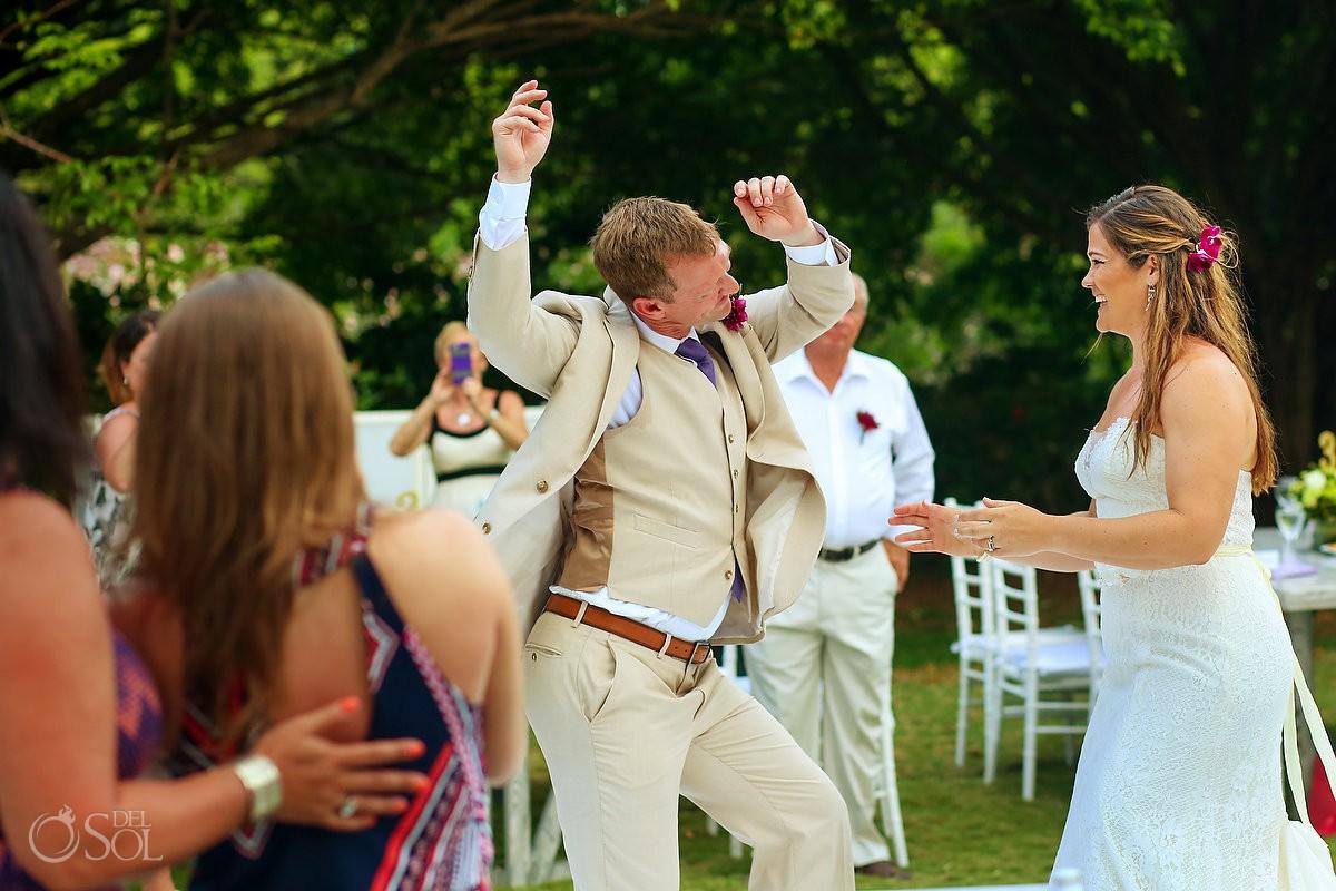 groom doing goofy dance entrance to destination wedding reception Dreams Tulum garden