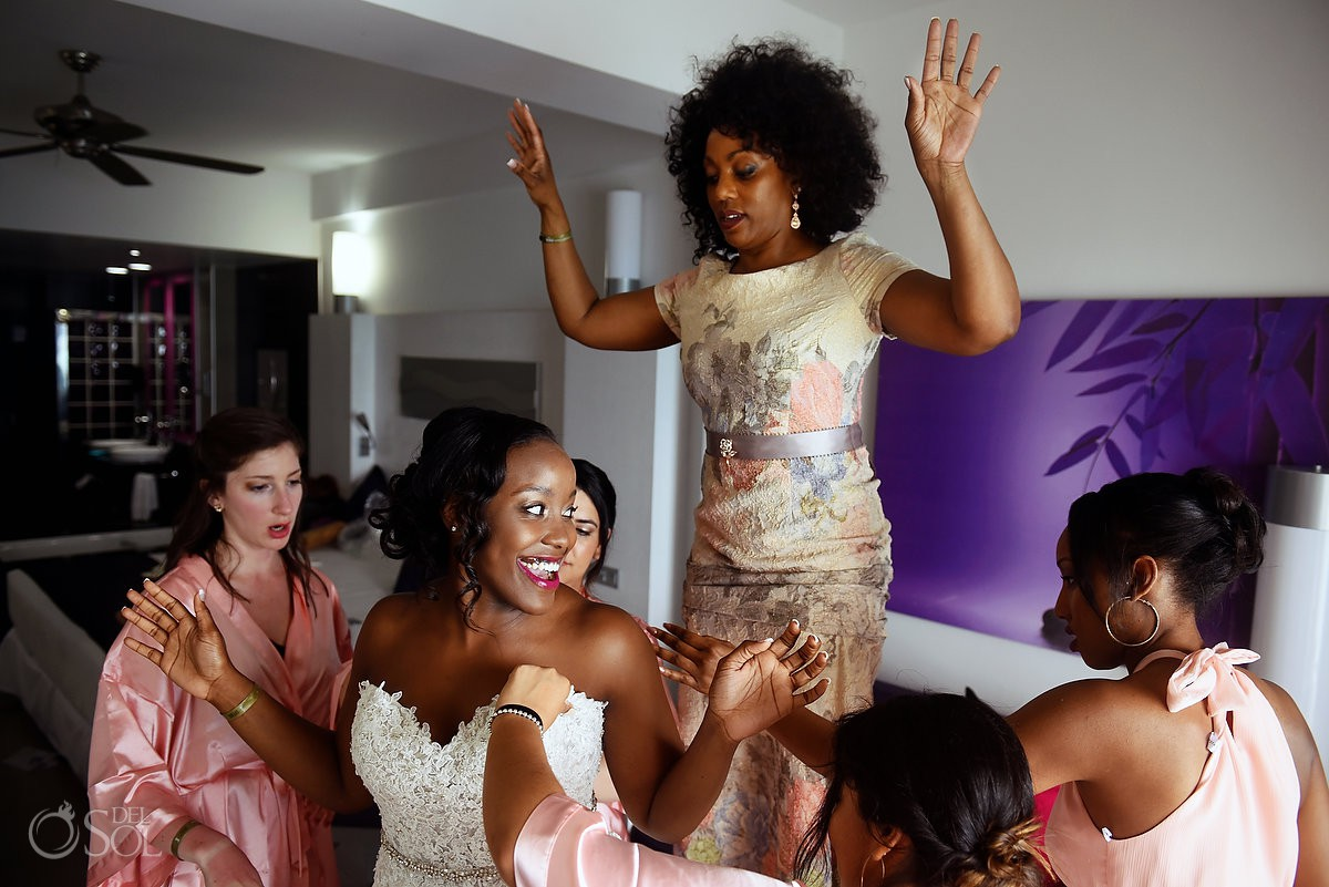 Happy bride putting on dress getting ready Destination Wedding Riu Palace Peninsula Cancun Mexico