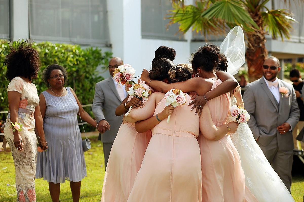 bridesmaids wearing peach dresses hugging Destination Wedding Riu Palace Peninsula Cancun Mexico