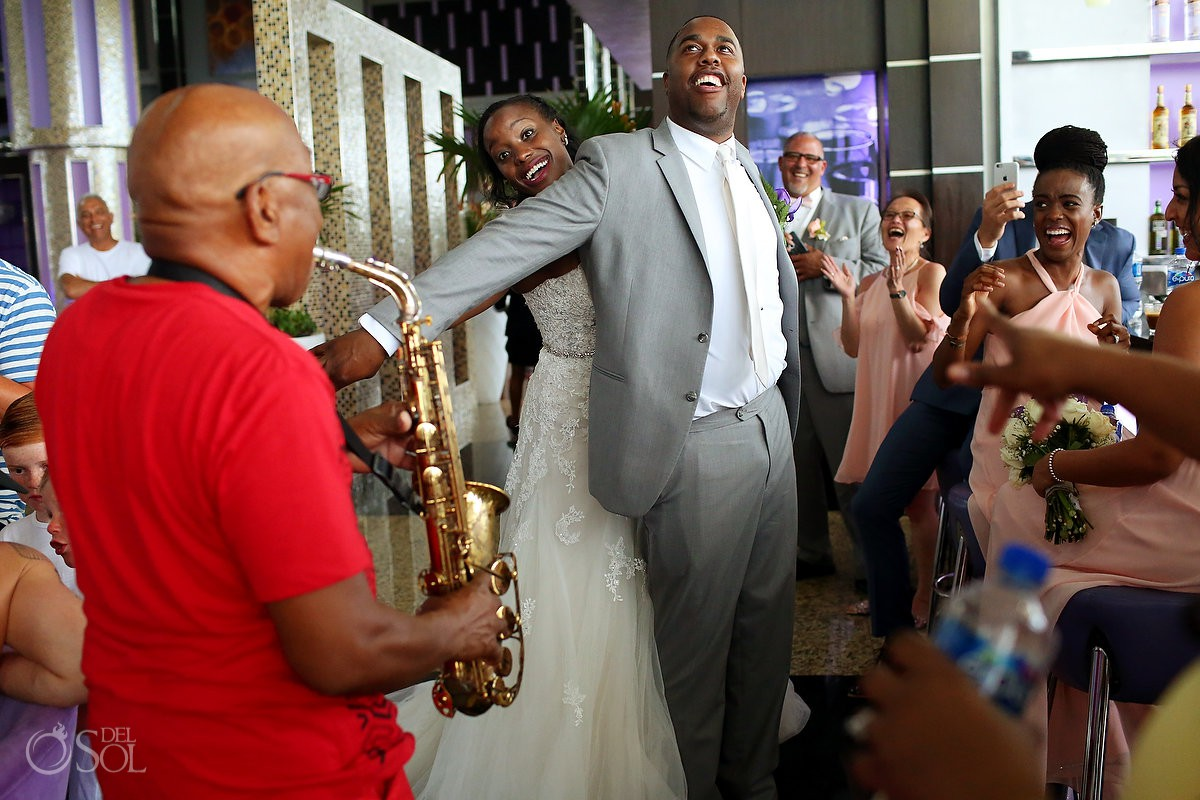 funny wedding photo groom doing Titanic pose to saxophone music Destination Wedding Riu Palace Peninsula Cancun Mexico