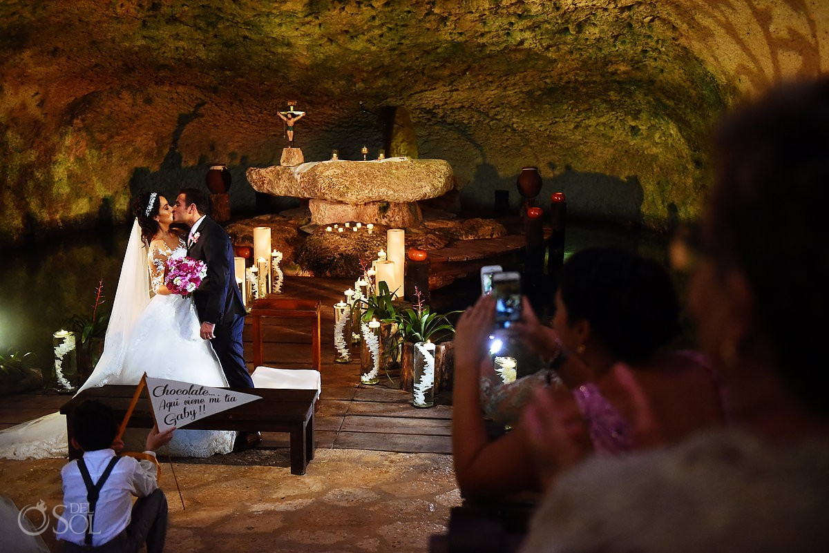 Novia y novio primer beso, boda ceremonia religiosa Xcaret Riviera Maya, Mexico