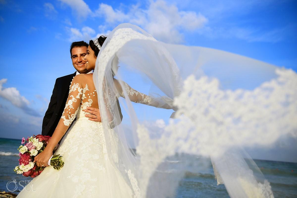 Retrato de novia y novio en la playa, velo volando, boda de destino Xcaret and Ocean Riviera Maya Mexico
