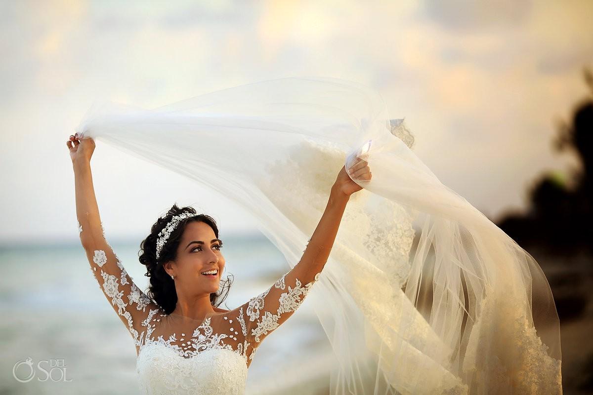 Retrato novia en la playa jugando con velo, fotografía creativa bodas de destino Xcaret and Ocean Riviera Maya Mexico