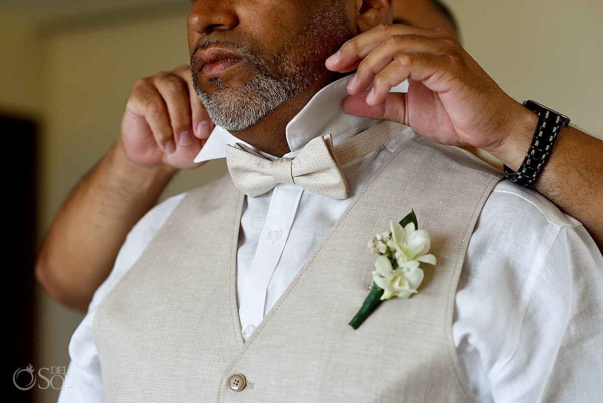 groom wearing beige vest and cream silk bow tie detail Now Jade Riviera Cancun Puerto Morelos Destination wedding