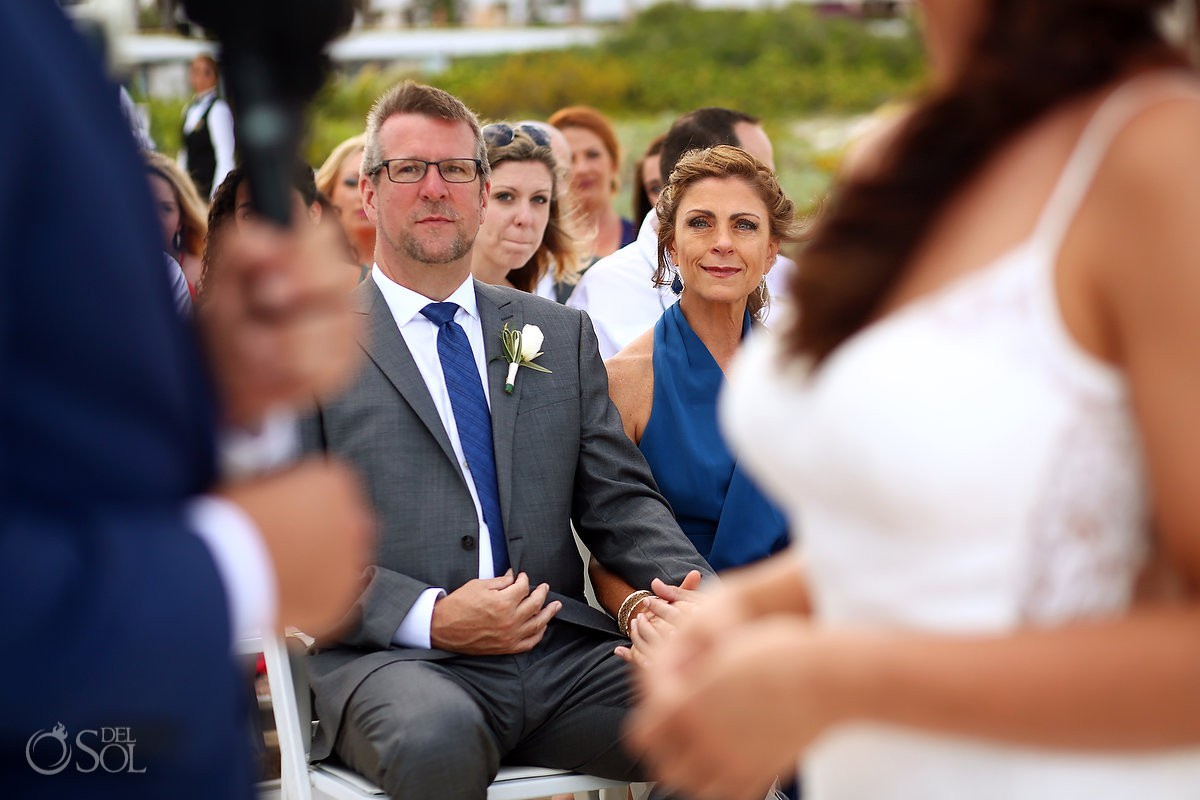 parents of bride watching reading vows beach destination wedding ceremony Secrets Playa Mujeres Golf and Spa Resort
