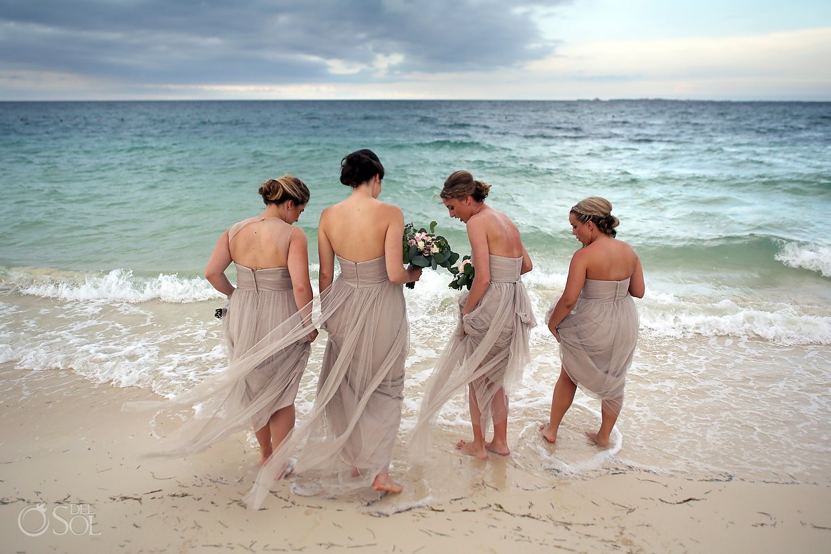 bridesmaids wearing blush pink dresses getting into the ocean Secrets Playa Mujeres Golf and Spa Resort