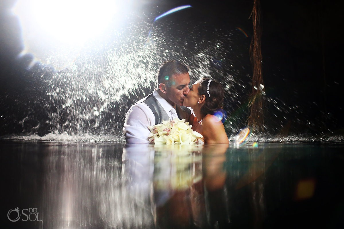 bride and groom kissing in the water holding bouquet cenote trash the dress Riviera Maya Mexico