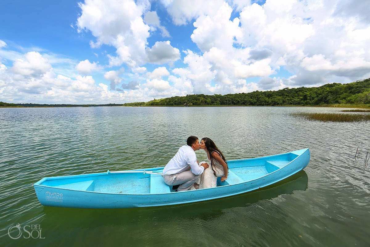 Bride and groom kiss at blue boat floating lagoon Riviera Maya Mexico Trash the Dress photoshoot