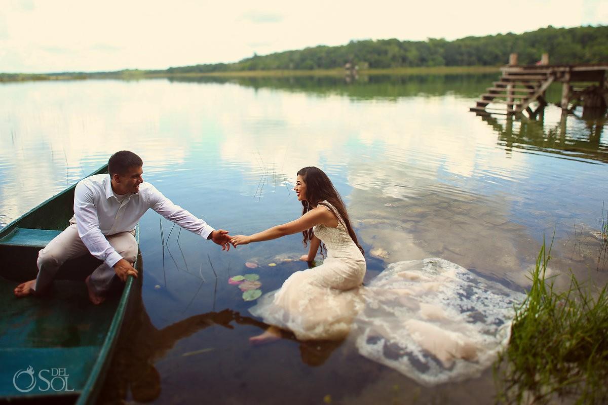 Groom reaches bride blue boat lagoon Riviera Maya Mexico Trash the Dress photoshoot