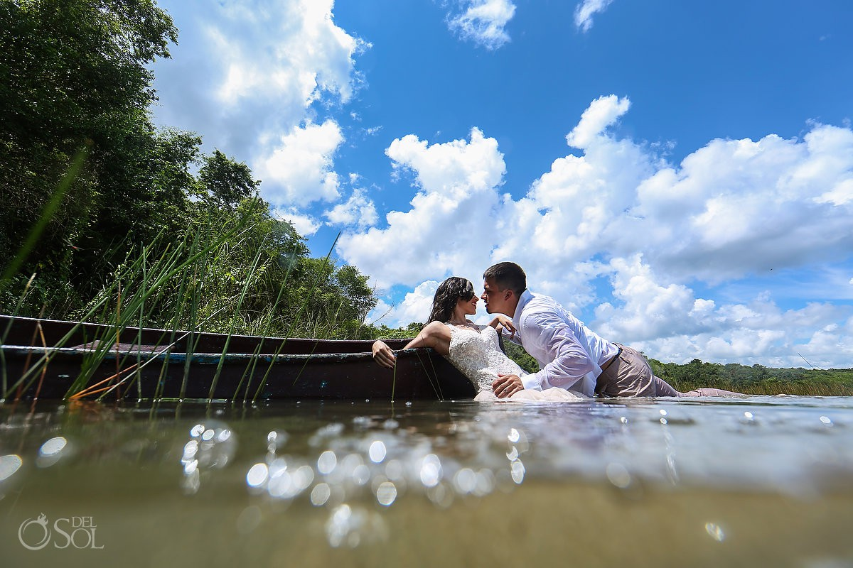 Bride and groom blue sky white clouds lagoon Riviera Maya Mexico Trash the Dress