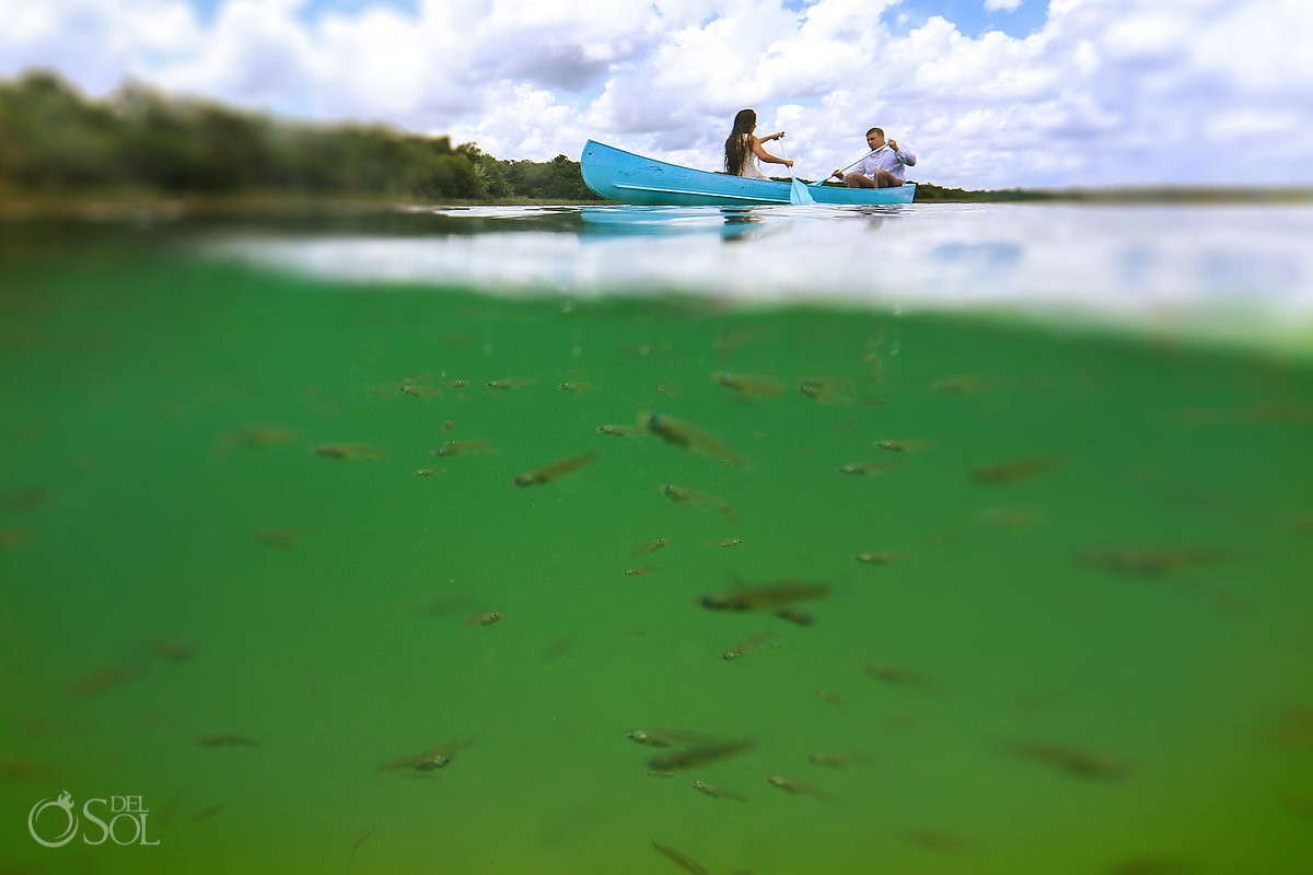 Little fish swimming around green water bride and groom rowing blue boat at lagoon Riviera Maya Mexico