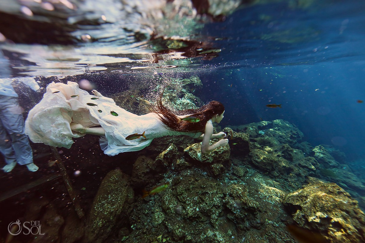 Fish swim next to bride dress during underwater photoshoot Trash the Dress cenote Riviera Maya Mexico