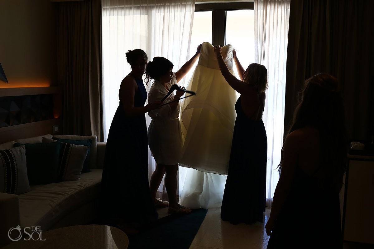 Getting ready Hyatt Ziva Cancun Photographer bridesmaids lifting Essence of Australia wedding dress