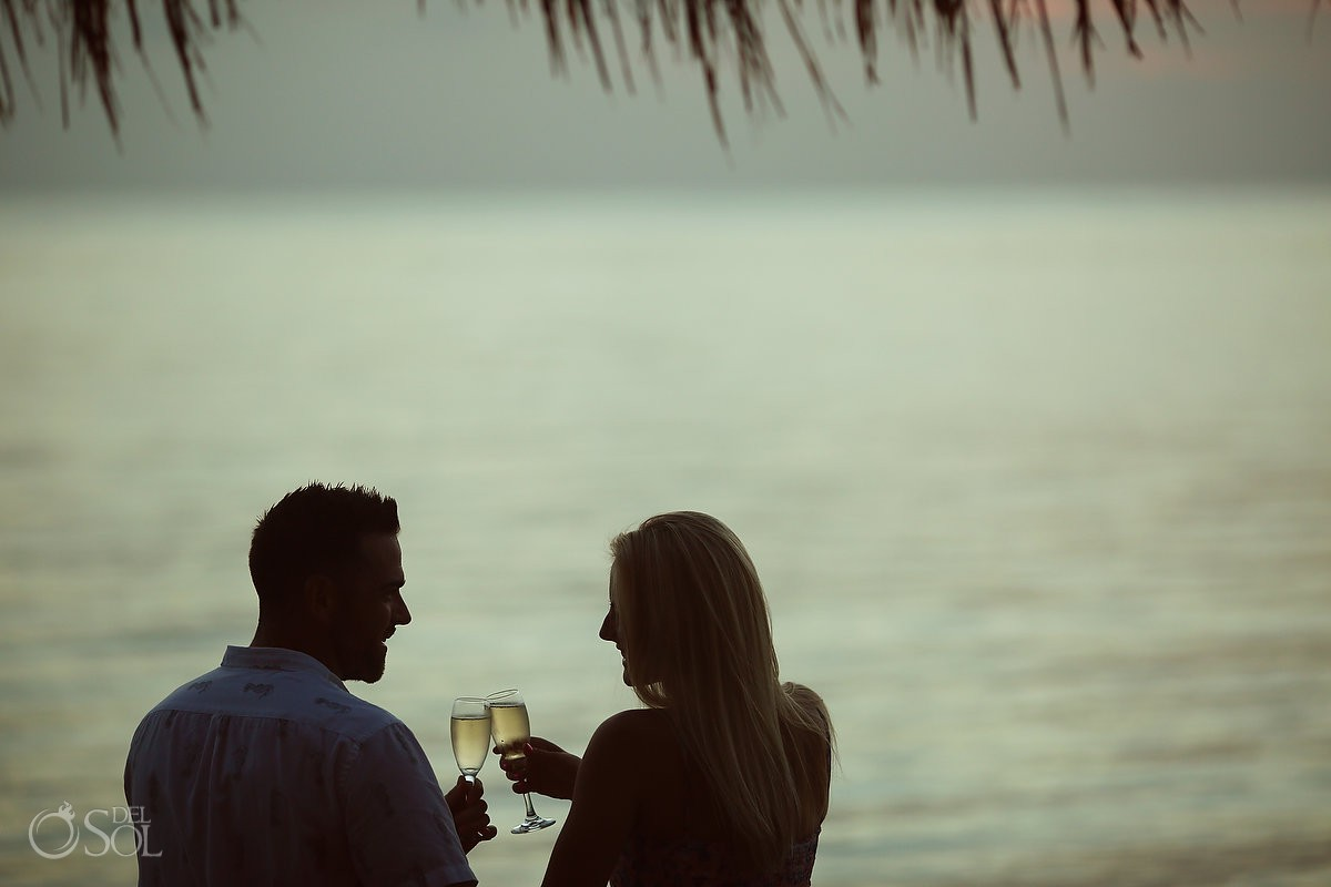 Cheers next to beach Engagement and Beach Portraits silhouette Secrets Aura Cozumel Cozumel Mexico
