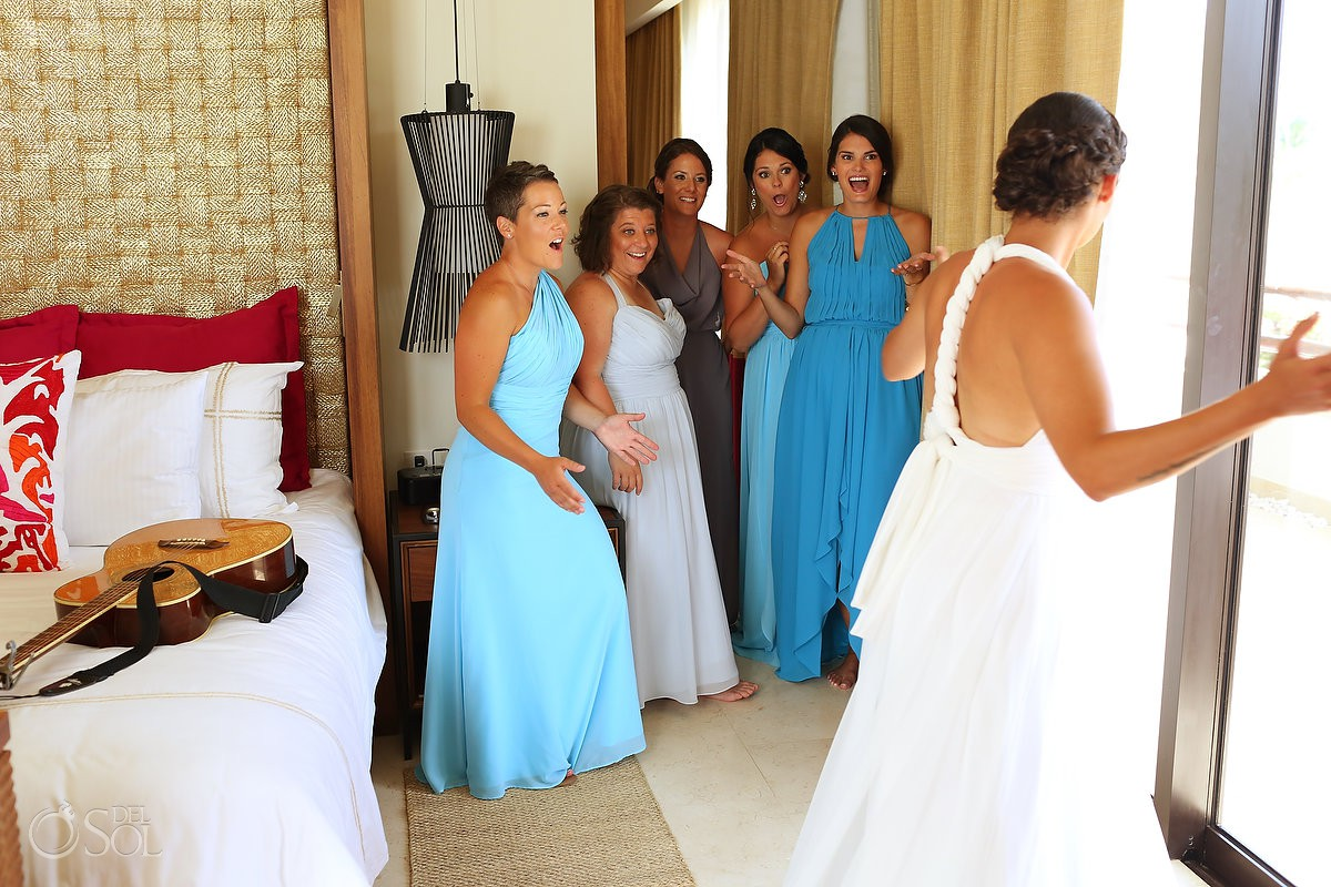 bridesmaids wearing long blue dresses looking at bride in her wedding dress
