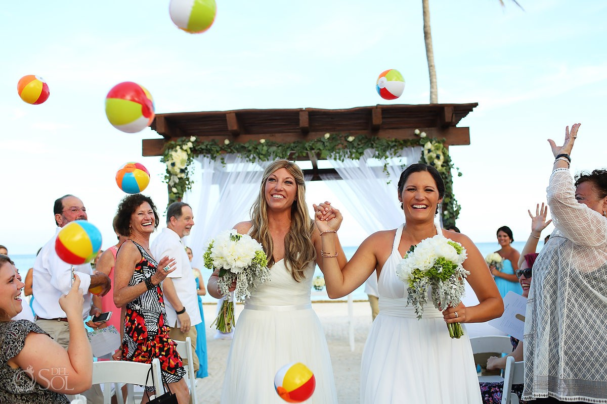 two brides exit wedding ceremony with guests throwing beach balls fun beach wedding idea Secrets Akumal Riviera Maya Mexico