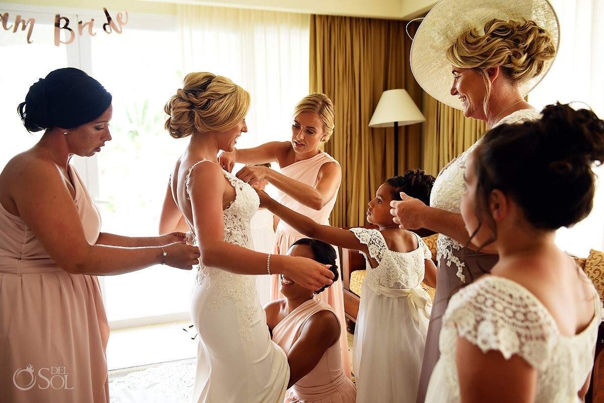 bride putting wedding dress on with help from family and friends getting ready Dreams Tulum Riviera Maya Mexico