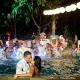 bride and groom kissing at pool wedding guest throwing water Grand Velas Riviera Maya Playa del Carmen Mexico