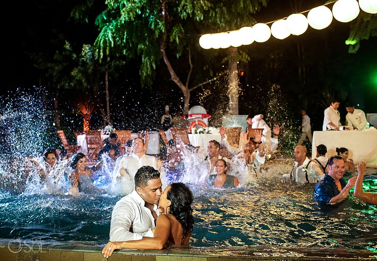 bride and groom kissing at pool wedding guest throwing water Grand Velas Riviera Maya Playa del Carmen Mexico