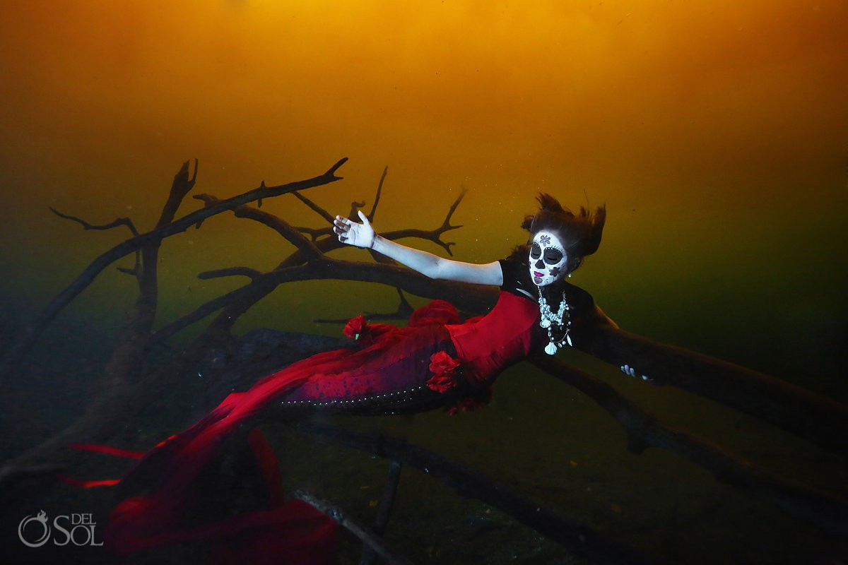 Frida Lemus free diver Catrina Sirena swimming around dead trees cenote Tulum orange water