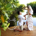 Kneeling down groom to be asks the question surprise proposal at the pier Andaz Mayakoba resort Riviera Maya engagement photographer del Sol Photographer