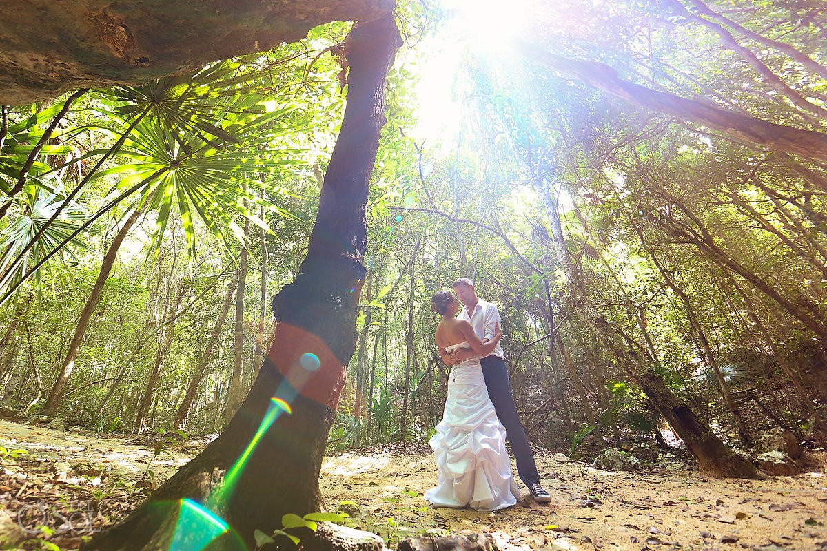 Beautiful sun light bride and groom middle of jungle Cenote Trash the Dress Riviera Maya Mexico.