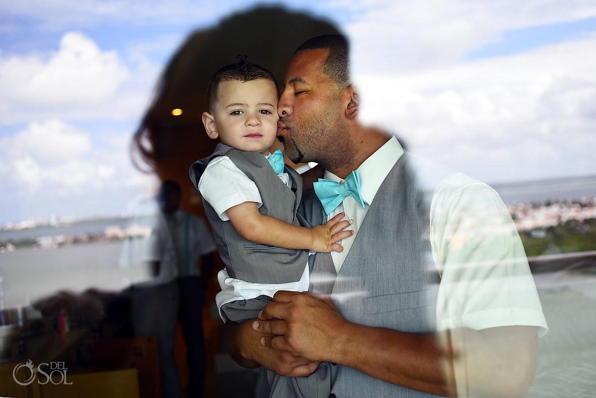 Groom kissing son Beach Palace Cancun Mexico