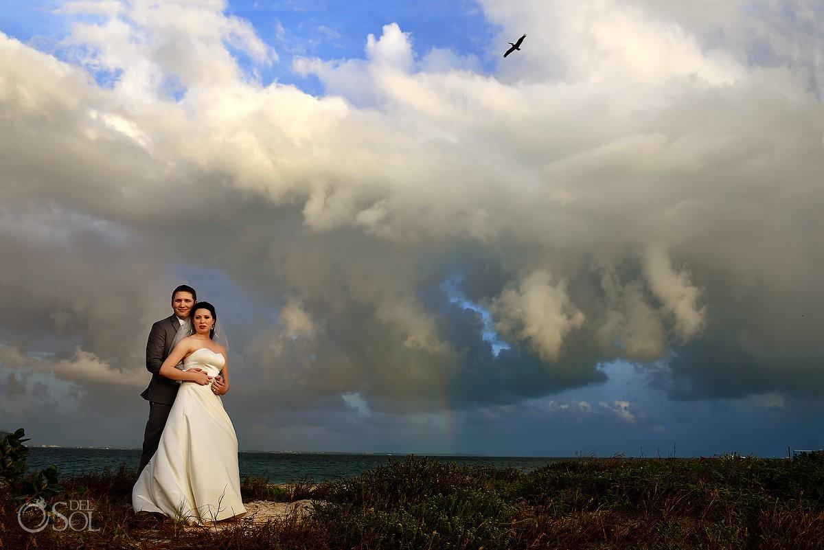 Bride and groom beach portrait birds and rainbow Destination wedding Finest Playa Mujeres Stone Gazebo Ceremony Cancun
