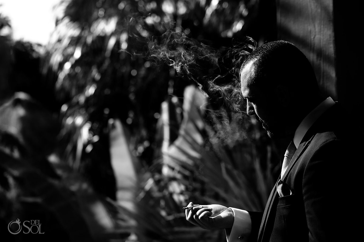 Artistic groom portrait smoking low key black and white photography