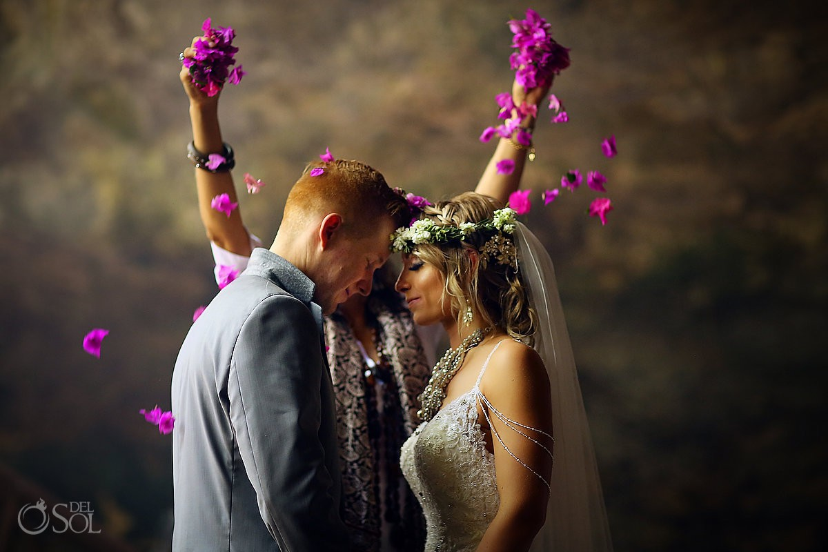 Cenote weddings shaman dropping pink flower petals on bride and groom Riviera Maya Mexico