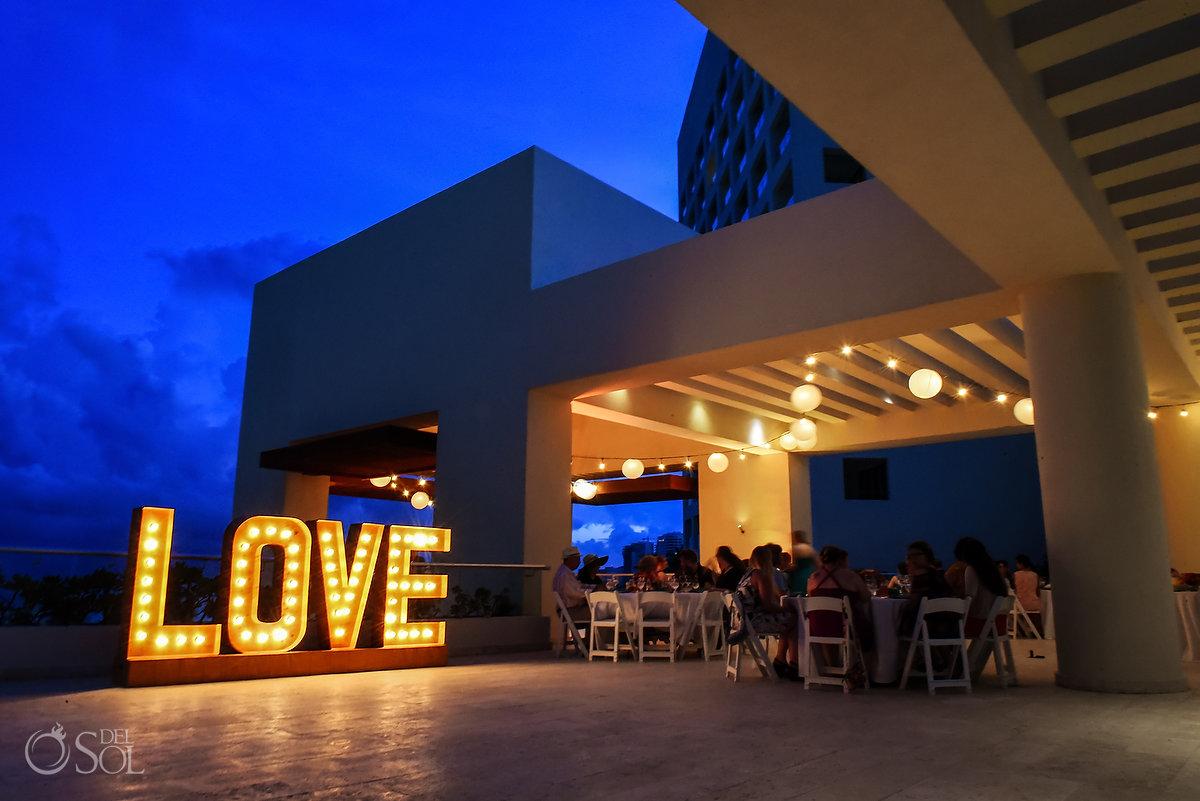 Destination wedding reception Hyatt Ziva Sky terrace illuminated love sign