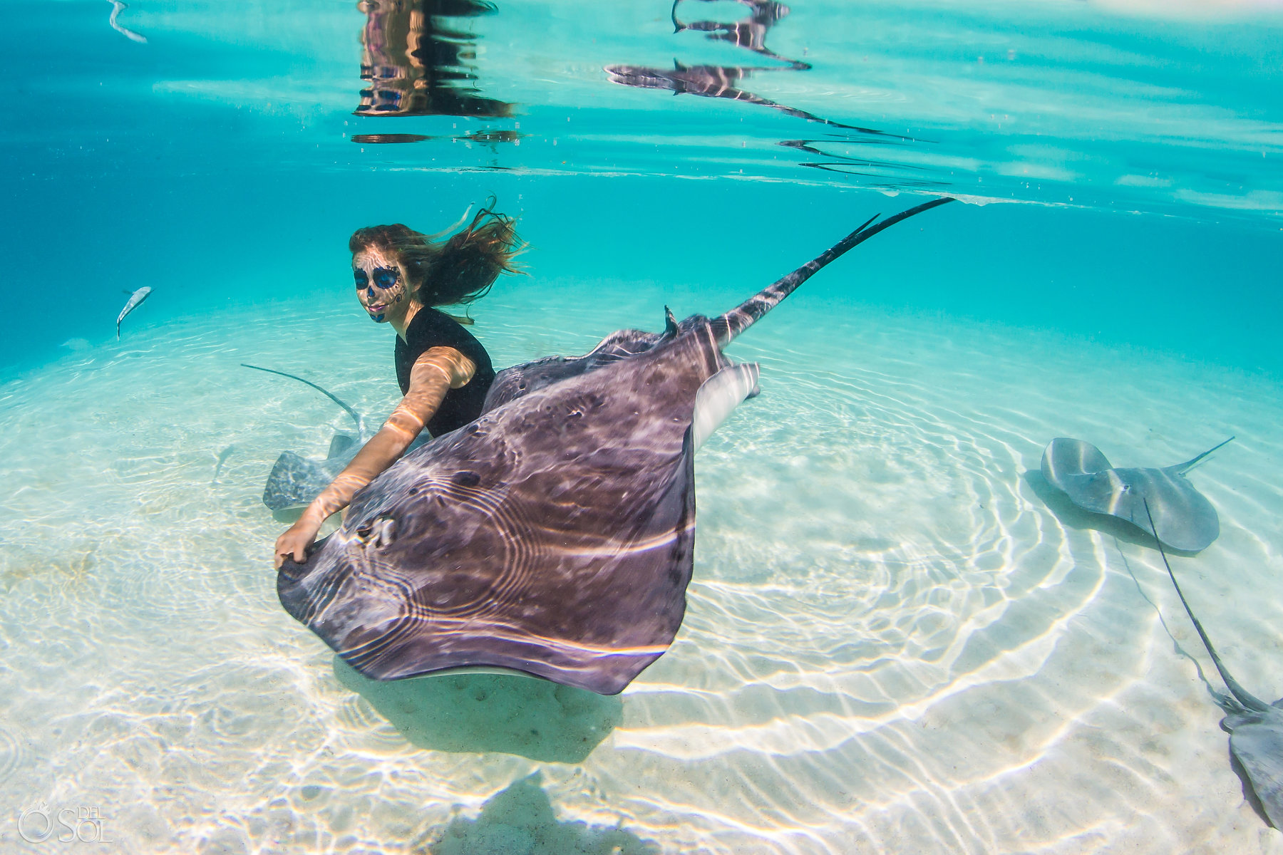Catrina Makeup woman playing with stingray light reflections clear amazing water white sand Tahiti underwater photography