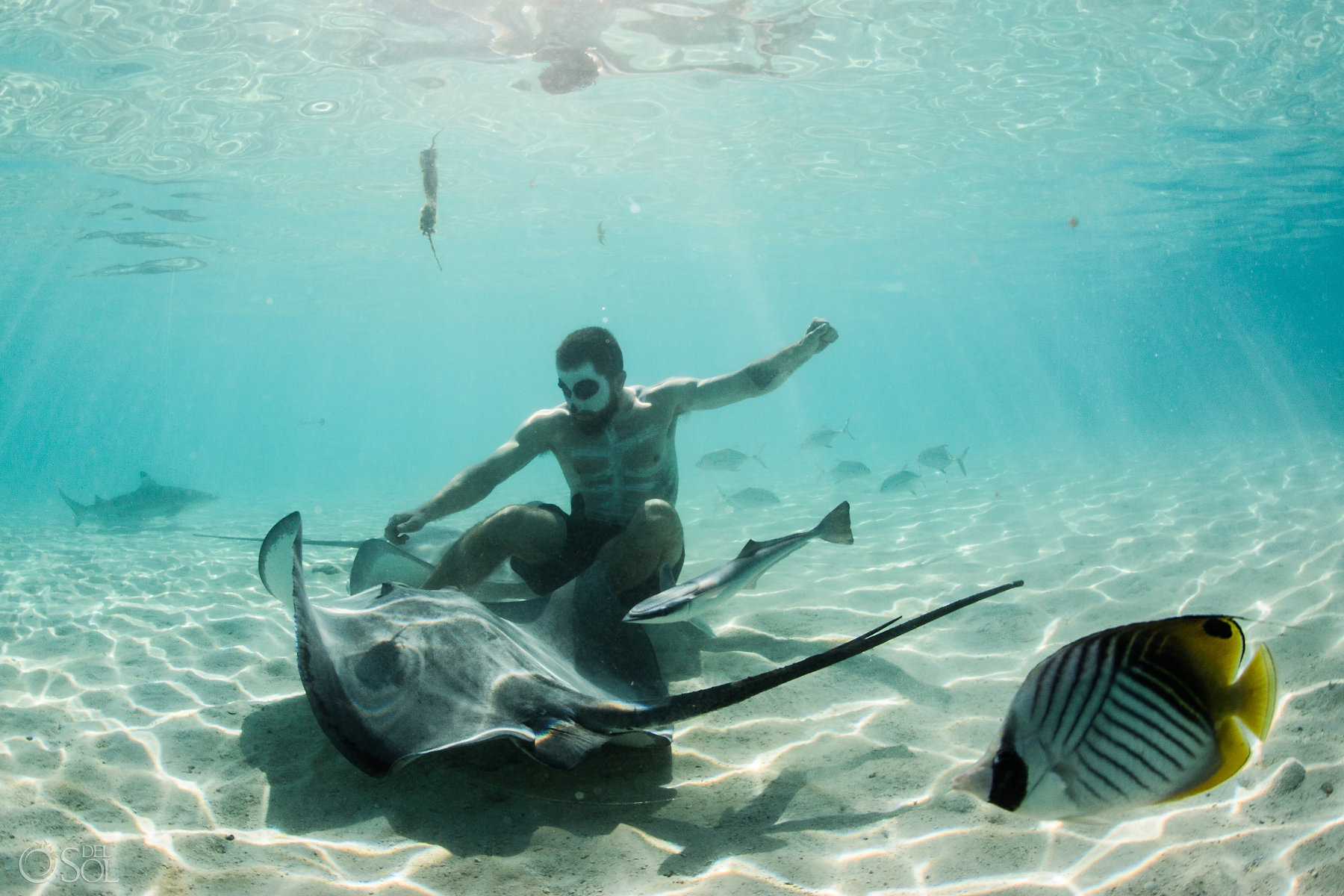 Catrina Makeup Men playing with stingray light reflections clear amazing water white sand Tahiti underwater photography