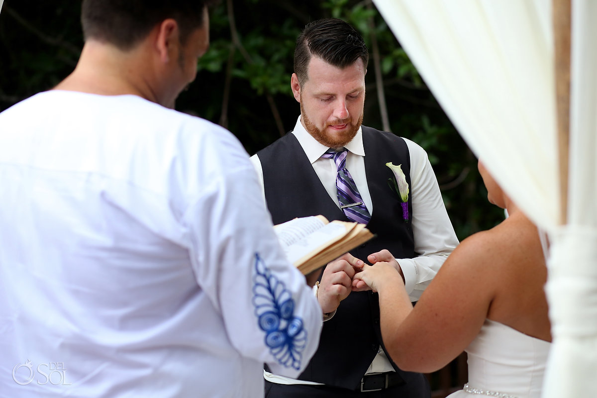 funny wedding photo groom sticking tongue out ring exchange