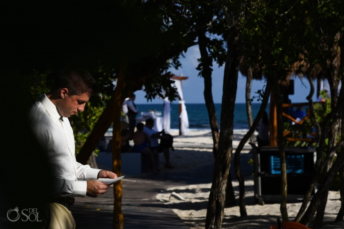 groom in a patch of sunlight reading his vows before his Iberostar Paraiso del Mar beach wedding