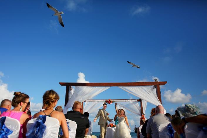 Seagulls flying high in the blue sky over wedding gazebo where bride and groom are celebrating #TravelForLove