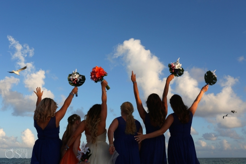 Wedding party photo ideas bride and bridesmaids with hands in the air with birs flying overhead Iberostar Paraiso del Mar Wedding