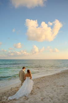 bride and groom walking on the beach at sunset wedding dress with long train dragging in the sand Iberostar Paraiso del Mar Wedding