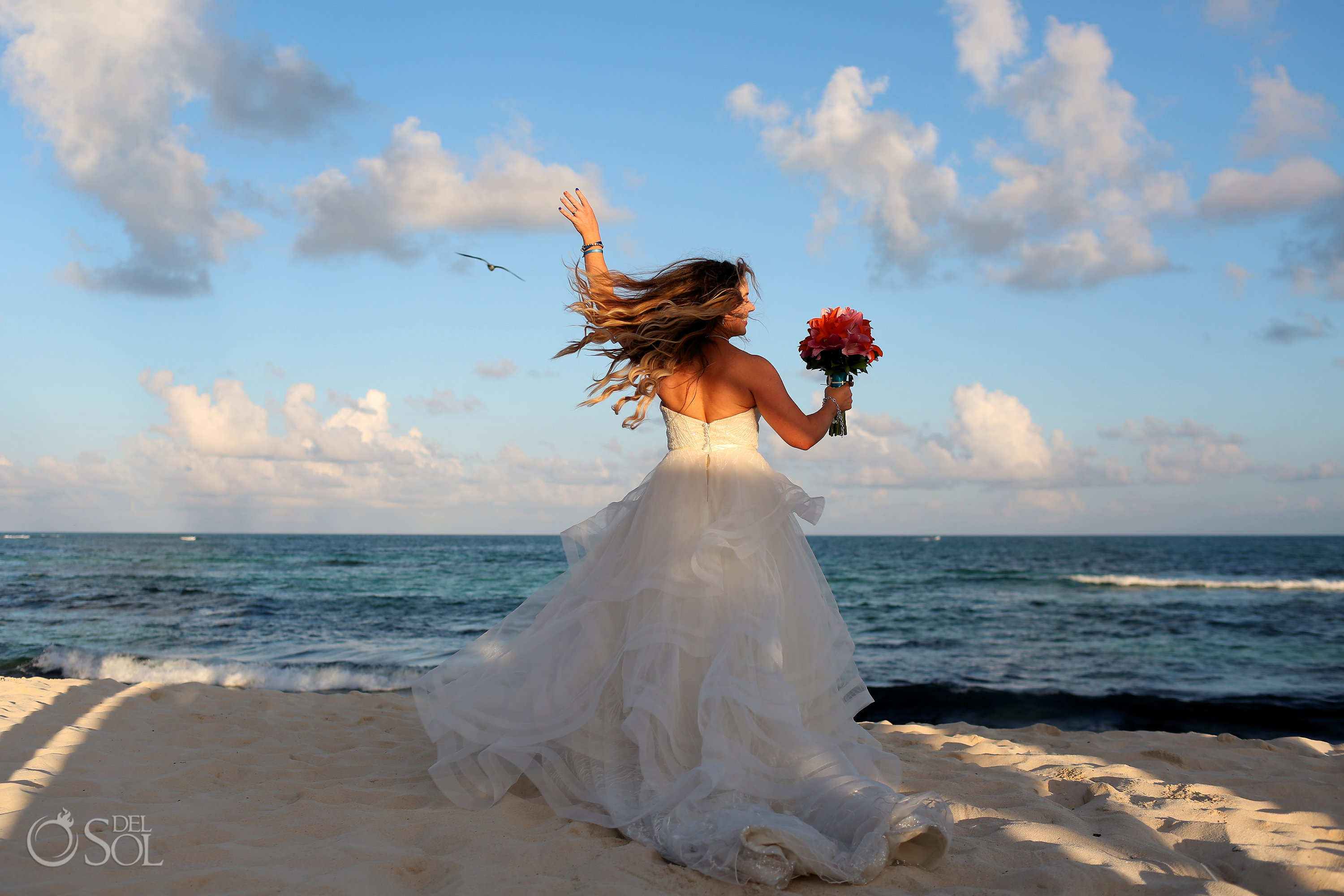 happy dancing bride spinning in her Matthew Christopher wedding dress with hair flying Iberostar Paraiso del Mar Wedding