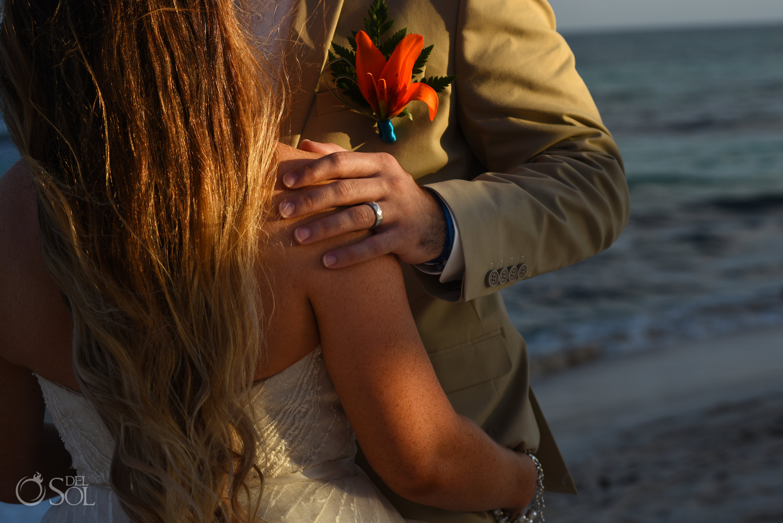 Grooms hand on brides shoulder with masculine geometric cut wedding band Iberostar Paraiso del Mar Wedding cancun