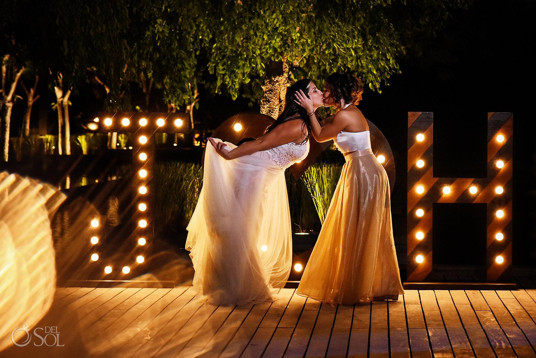 Nizuc same sex wedding two brides kiss on Akan terrace in front of custom J H illuminated sign #loveislove