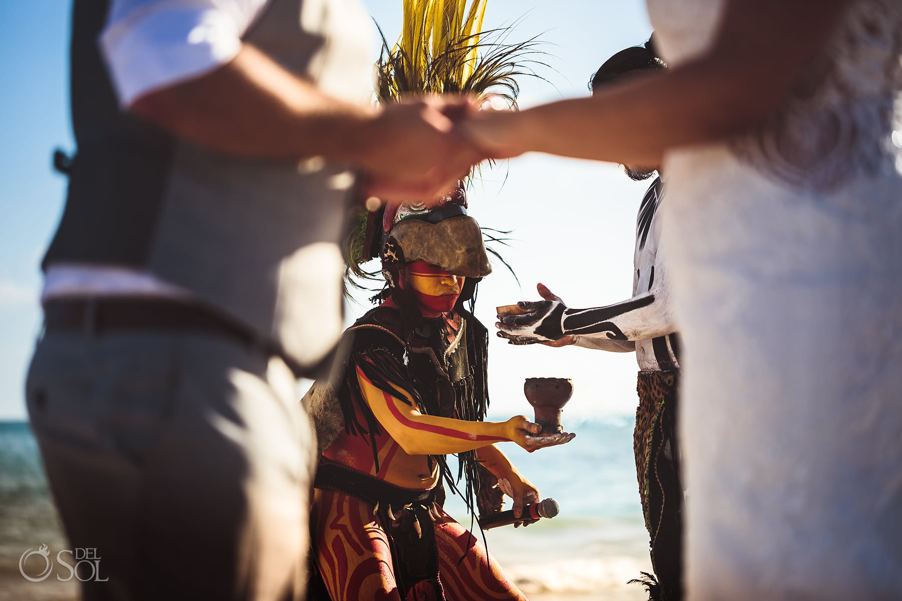 Mayan warrior wearing feathered headdress red yellow body paint blessing bride and groom with copal incense Dreams Tulum