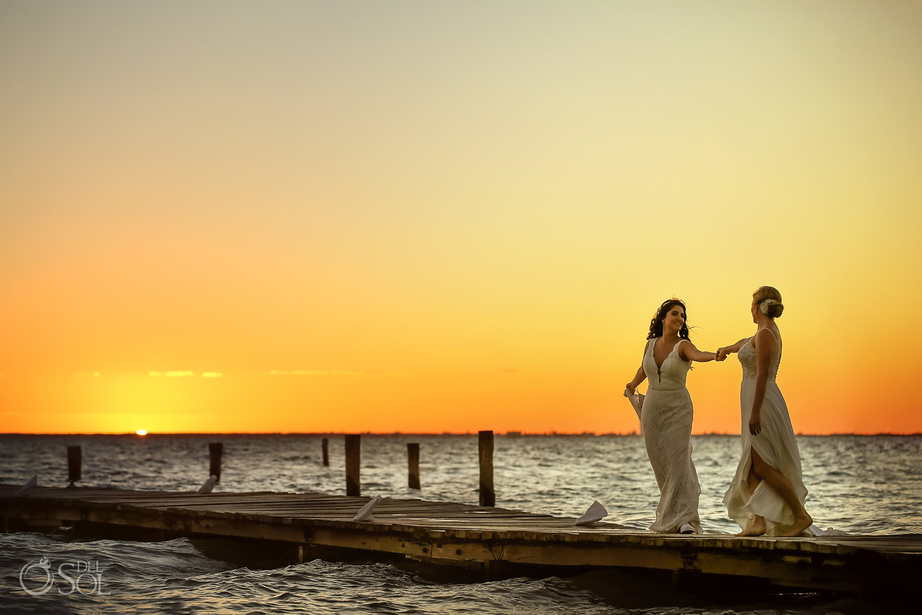 Lesbian brides over a pier photo session Isla Mujeres queer wedding Zama Private Beach