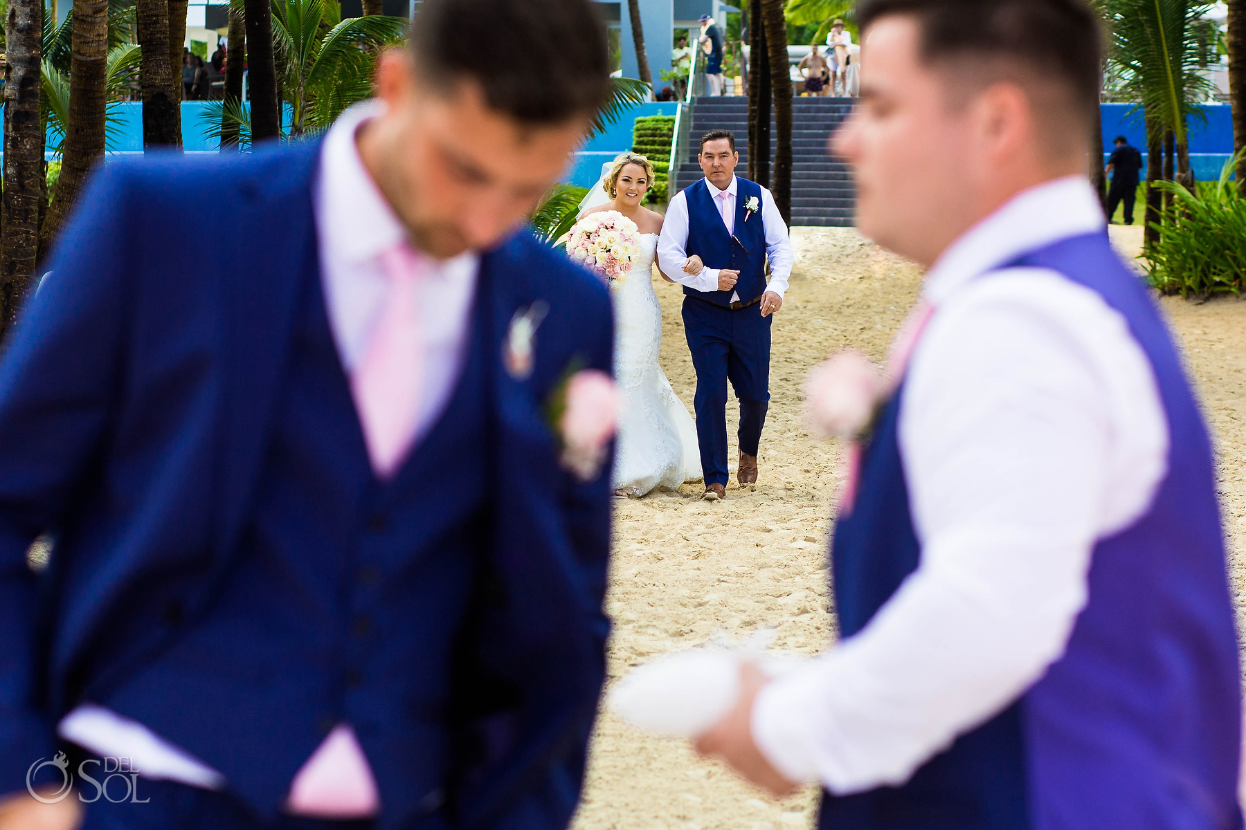 Bride walking with dad true the beach sand