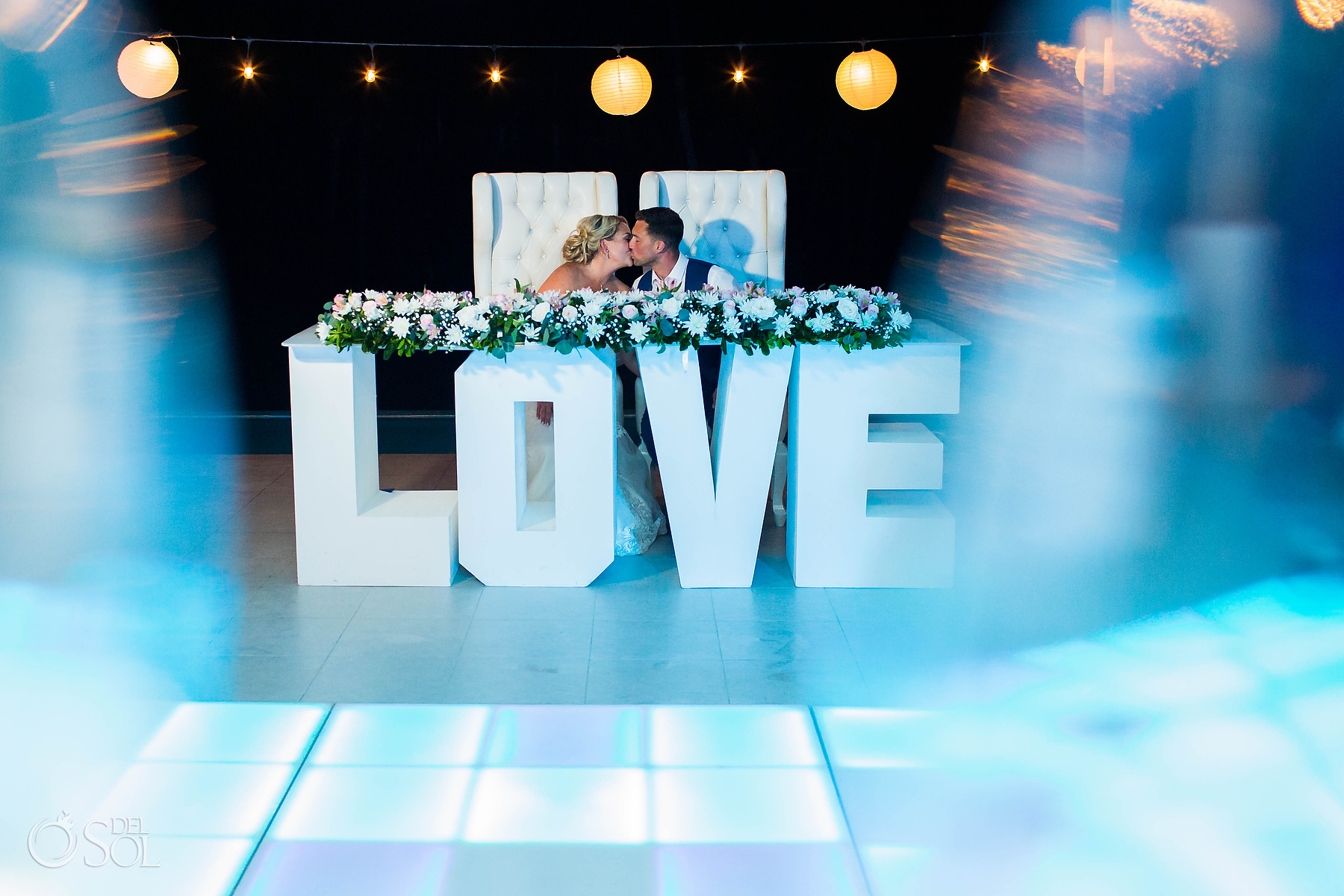 Bride and Groom kissing during the wedding reception Love big letter decoration Riu Palace Mexico